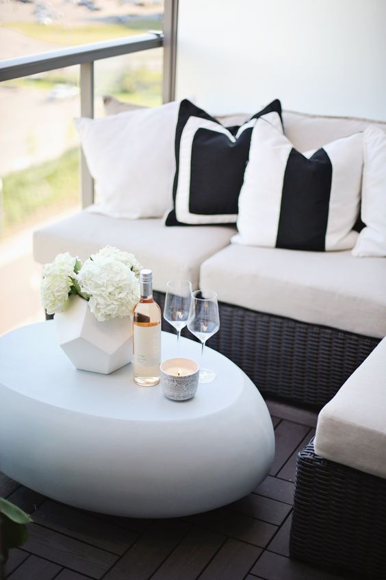 a corner wicker bench with comfy cushions and a modern egg-shaped white table