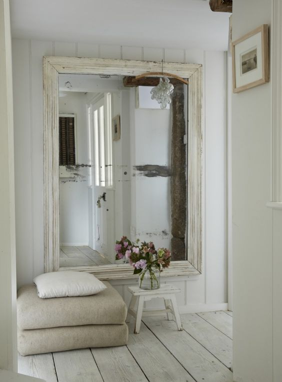 an oversized mirror in a whitewashed frame for a Scandinavian entrance