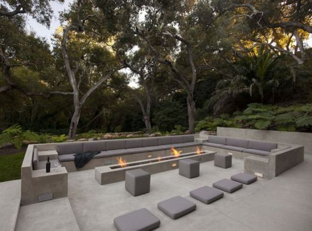 minimalist stone outdoor conversation pit with benches and a long narrow fireplace