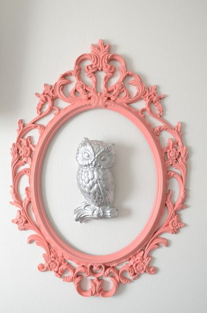 cool pink ornate frame around a sculptural owl