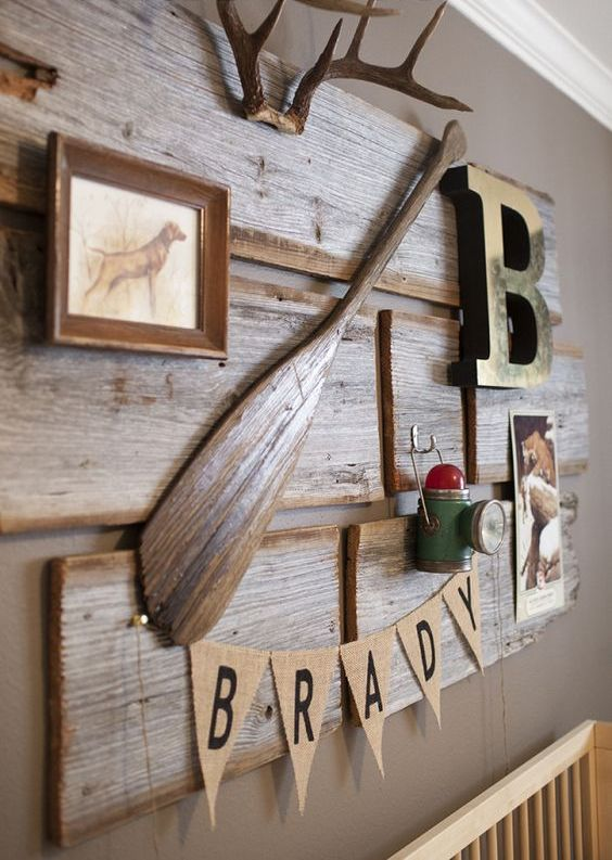 reclaimed wood artwork with antlers, an oar, a monogram and a framed piece