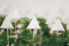 18 small faceted white pots with greenery and toppers look unusual