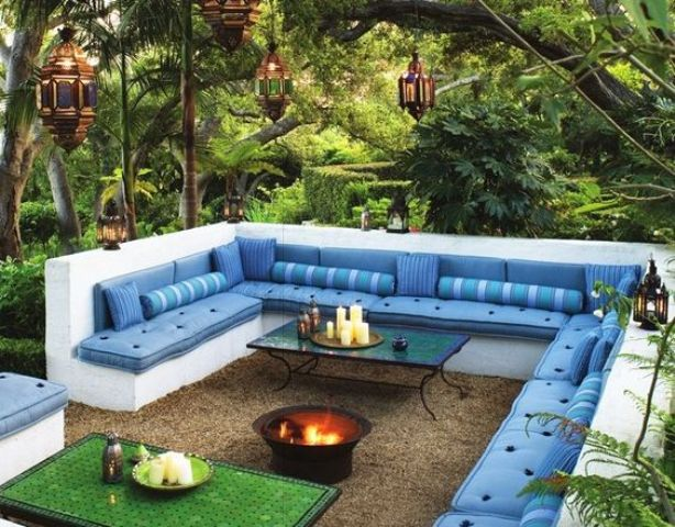 white concrete conversation pit with a fire bowl and tables