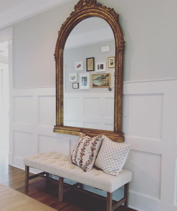 curved mirror in a large wooden frame with an antique feel