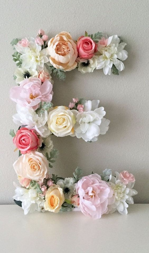 letter art piece made of faux flowers is the cutest idea for a girlish space
