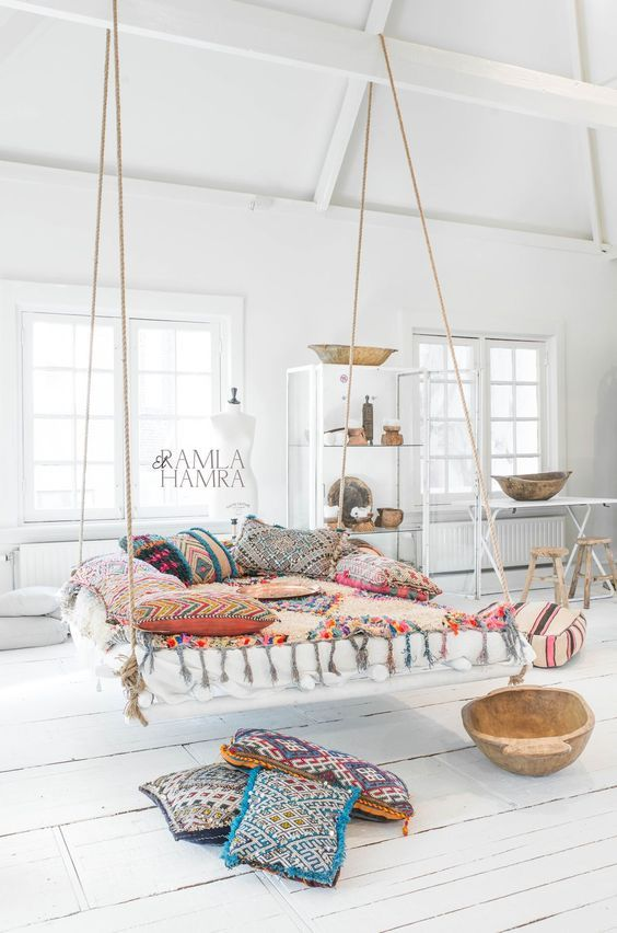 a boho and gypsy bedroom with a hanging bed and colorful textiles