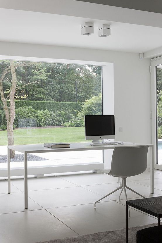 a minimalst white home office with a panorama window and garden views