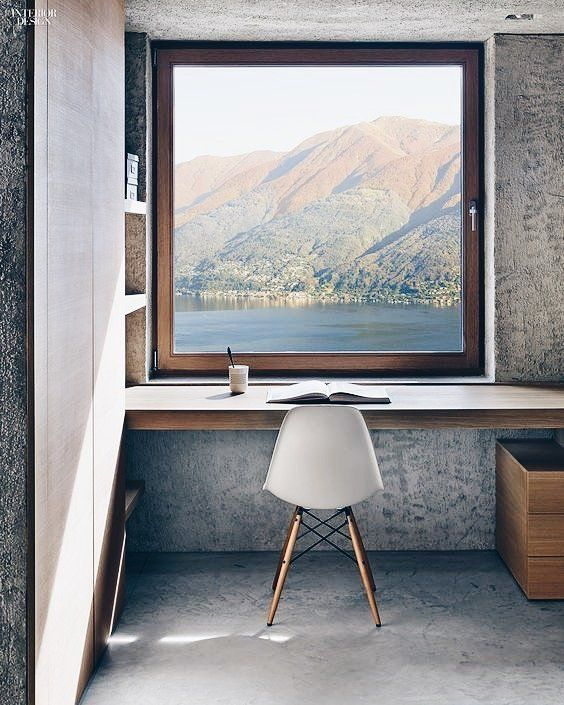 a minimalist home office with a windowsill as a desk and a gorgeous lake view
