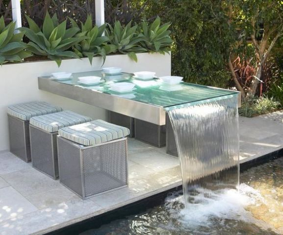 a built-in outdoor table with a waterfall design and metal stools