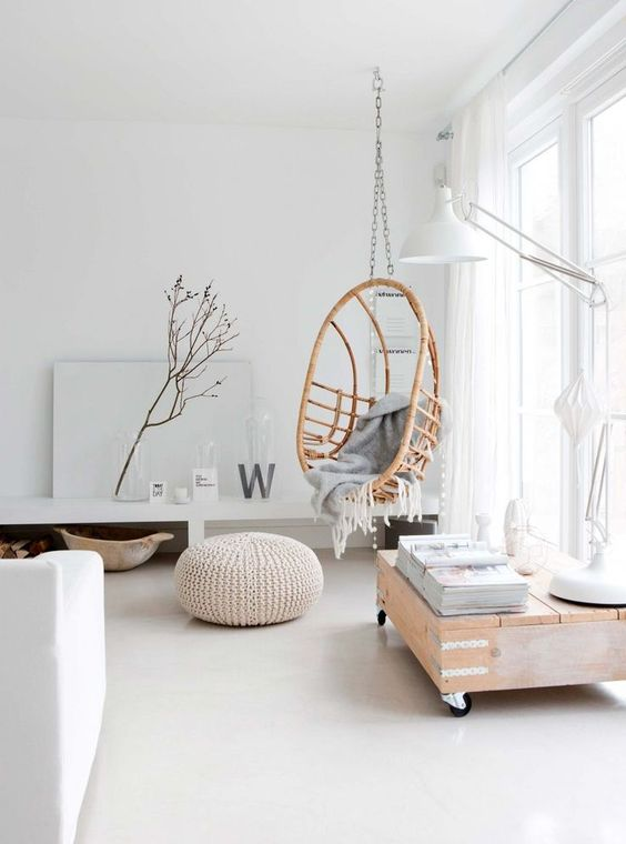 a rattan hanging chair on a chain makes the interior warmer