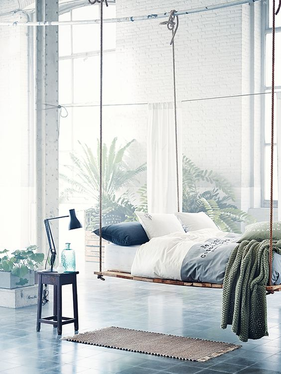 a light-filled and airy bedroom with a bed hanging on ropes