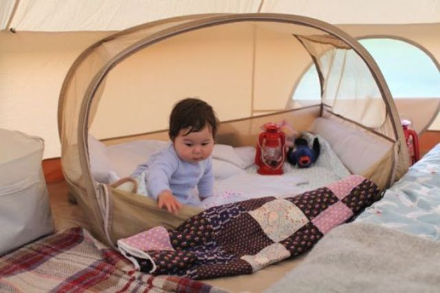 a small outdoor baby tent in beige placed inside an adult's tent