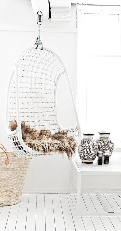 a white wicker hanging chair with faux fur for a Scandinavian interior