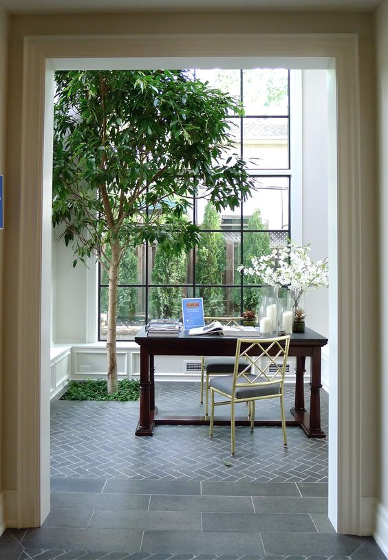 a large black frame window with a garden view and a tree growing inside for more freshness