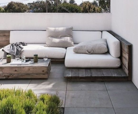 a weathered corner wood seating with white cushions and pillows