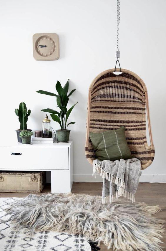 striped wicker chair suspendedin a living room makes the ambience relaxing