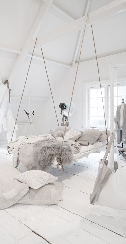 a whitewashed boho chic bedroom with a hanging rop bed