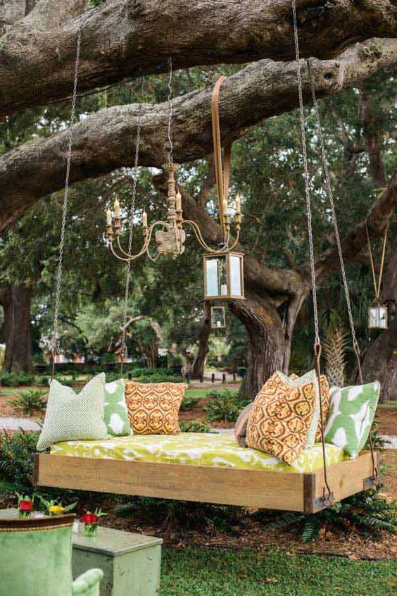 a comfy hanging bed for one attached to a tree in the garden