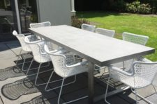 11 a modern concrete table and white metal chairs for a simple dining space