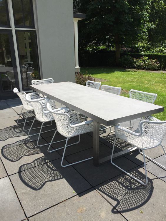 A Modern Concrete Table And White Metal Chairs For A Simple Dining Space
