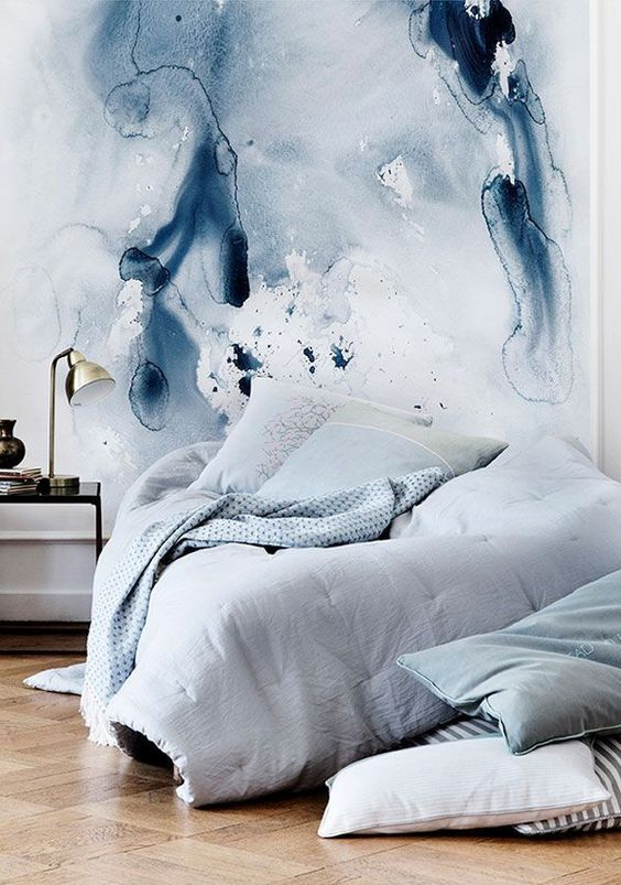 watercolor wall continues the bedroom decor in blues