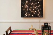 13 a black constellation artwork with lights makes the dining space eye-catchy