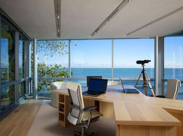 a modern home office with a desk and fully glazed walls with gorgeous sea views