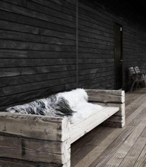 a weathered wood seat with armrests and a faux fur cover