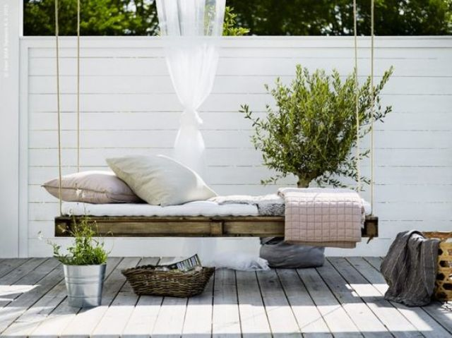 a whitewashed Scandinavian backyard with a pallet hanging bed