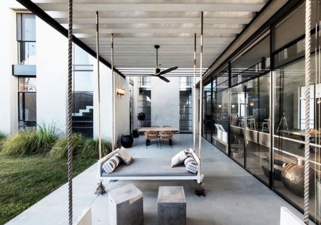 an outdoor space with a dining zone, concrete stools and a hanging bed