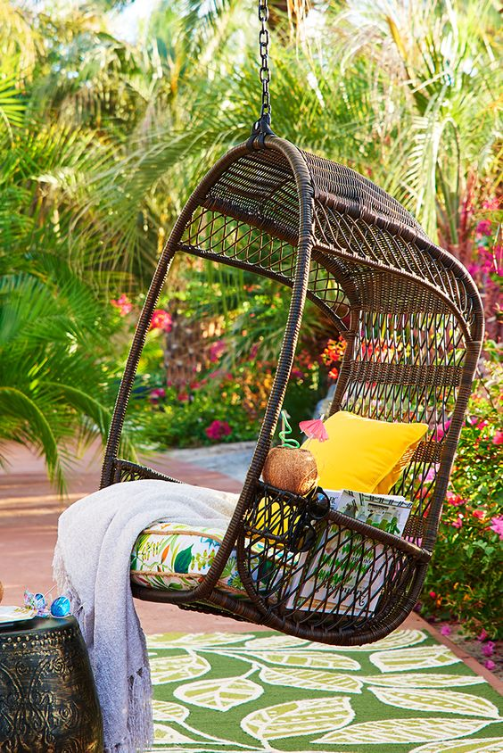 dark swinging hanging chair with a cushion for an outdoor space