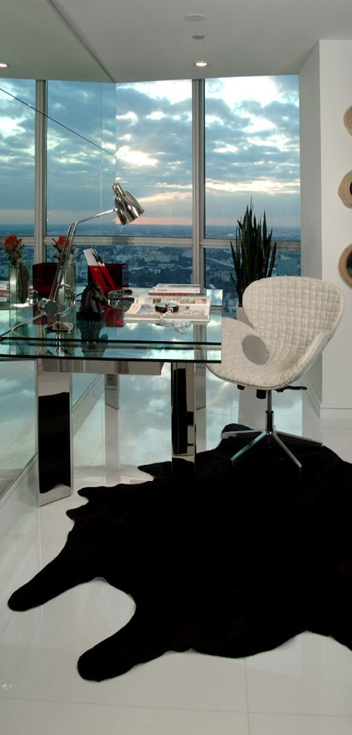 edgy home office with a glass desk and a city view