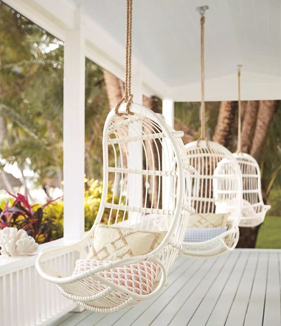 white hanging rattan chairs on a porch to make it relaxing and dreamy