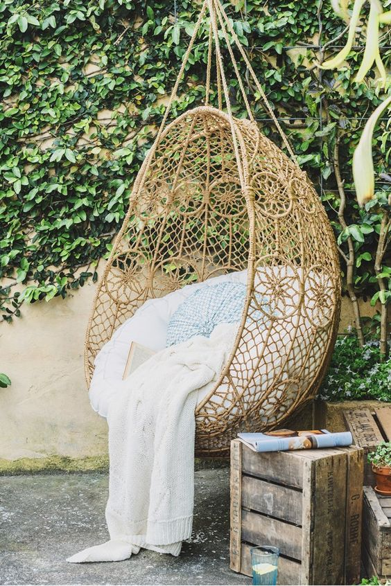 wicker egg-shaped chair suspended in an outdoor space for relaxation