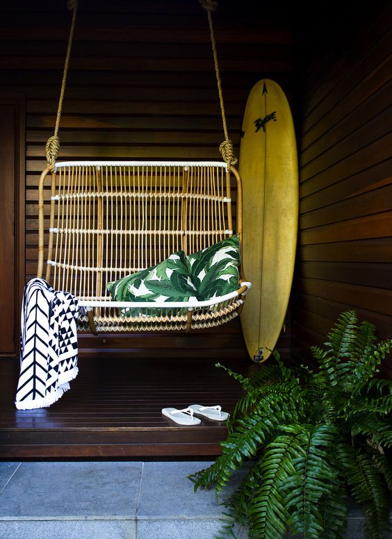 a 70s inspired rattan swing with a couple of pillows and a geo blanket looks very chic