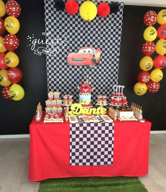 a Cars-themed dessert table with a checked fabric backdrop, black, red and yellow decor