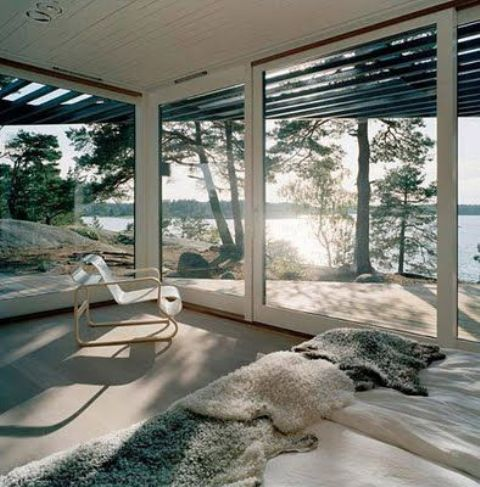 a bedroom with glazed walls and amazing forest and lake views looks amazing