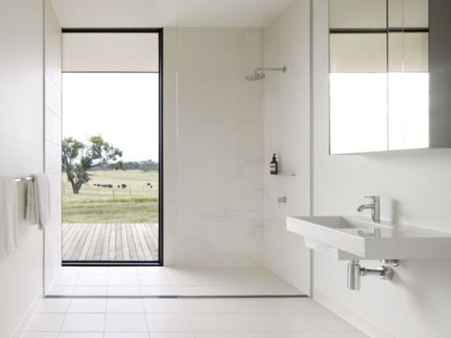 a clean white bathroom with a partially glazed shower wall to keep privacy and enjoy views when there's no one looking