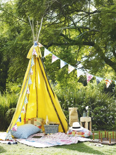 a colorful yellow teepee with printed blankets and pillows and fabric garlands