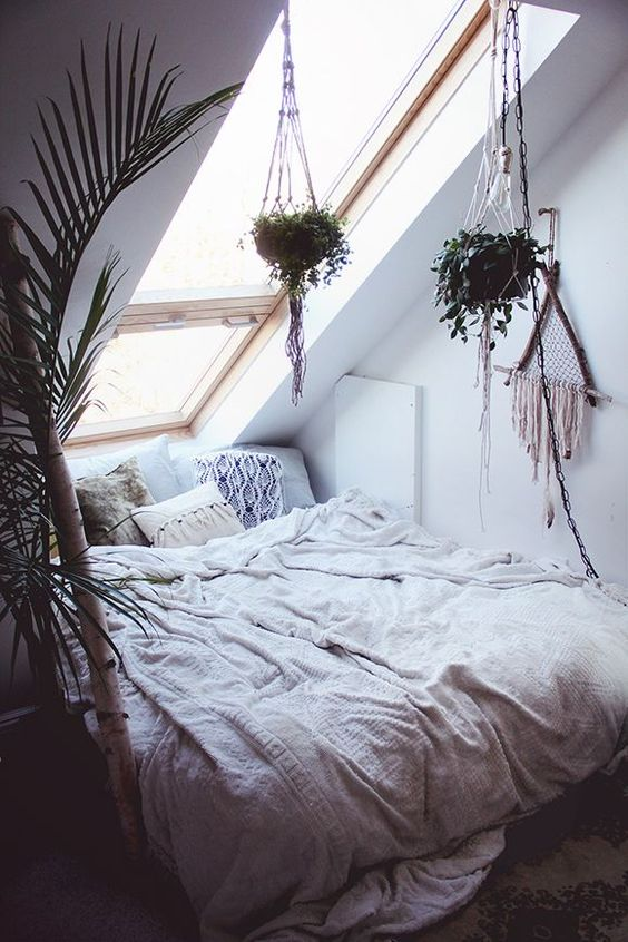 a small attic bedroom with a skylight as the only window looks very cozy and wlecoming