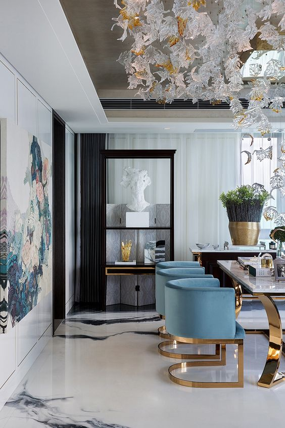 light blue velvet chairs with gold legs add chic to this exquisite dining space