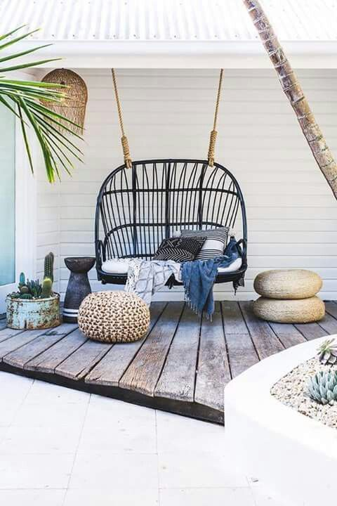 a beachside deck with a black rattan swing and some black and white pillows looks trendy