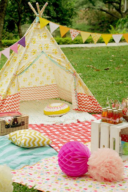 a bold printed teepee with colorful blankets and pillows, ideal for kids' games