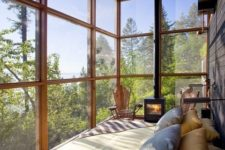 03 a cozy fully glazed bedroom with a hearth and forest views