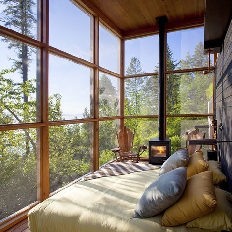 a cozy fully glazed bedroom with a hearth and forest views
