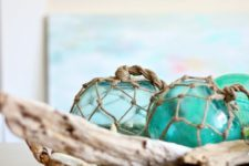 03 a rattan basket with driftwood and large glass buoys for a mantel display