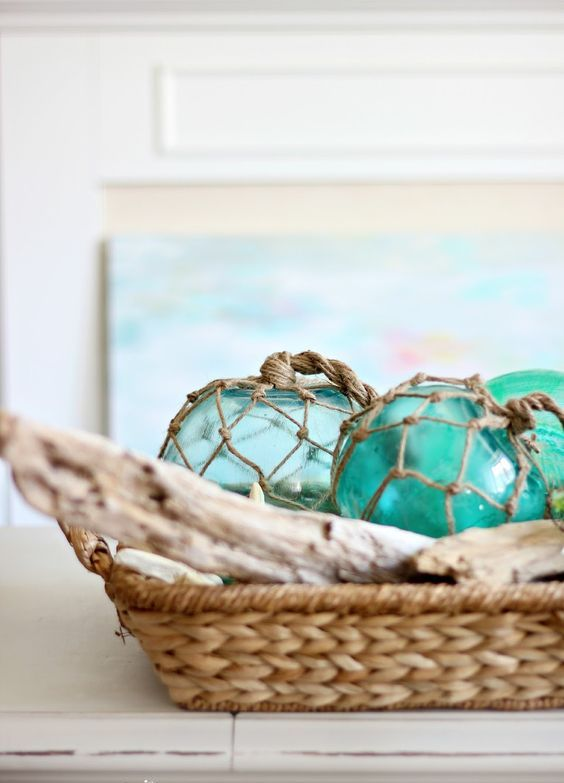 a rattan basket with driftwood and large glass buoys for a mantel display
