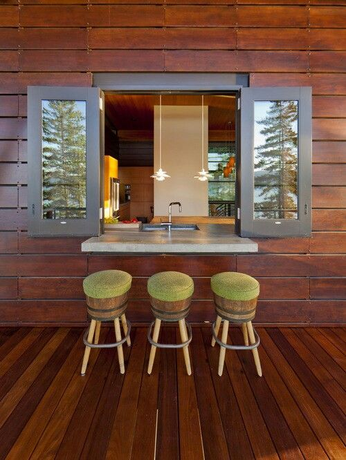 a rustic space clad with wood, dark stained wood framed window
