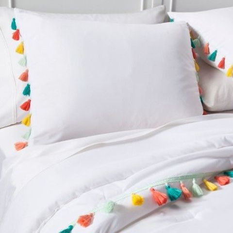 spruce up simple white bedding with colorful tassels for summer, this is an easy craft
