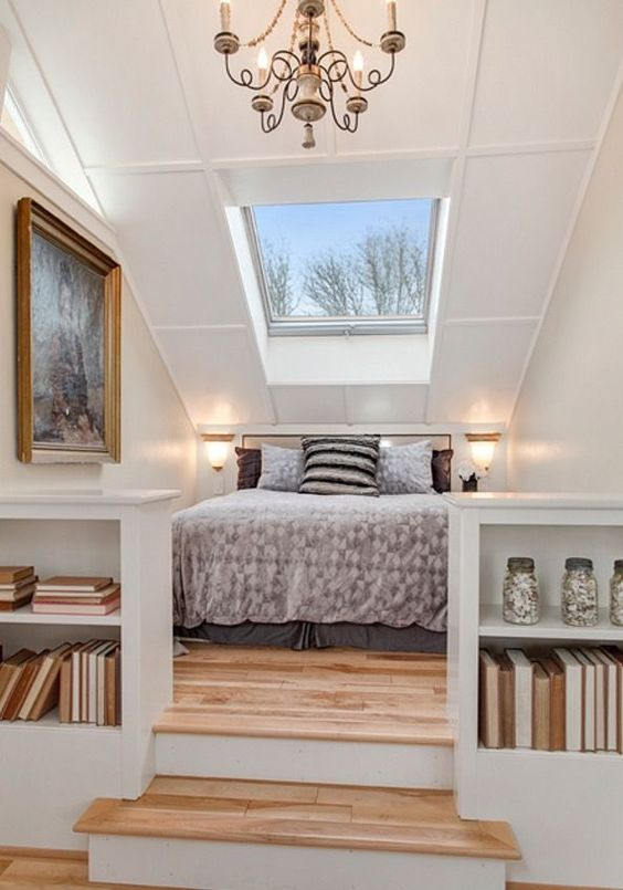 a bedroom nook in an open space is defined with steps and a skylight that fills it with light